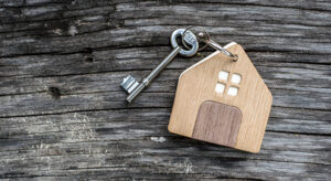 key with shaped house keychain on chain on wood texture background. Idea: buying a house, renting, selling real estate. Mortgage.